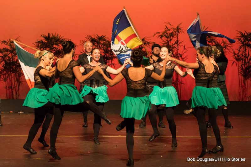 Women dancers in green skirts, black top and tights. Men in background with flags waving.