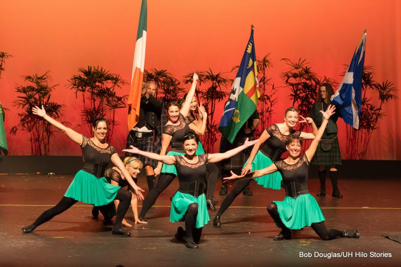 Women dancers in green skirts, black top and tights. Men in background with flags.