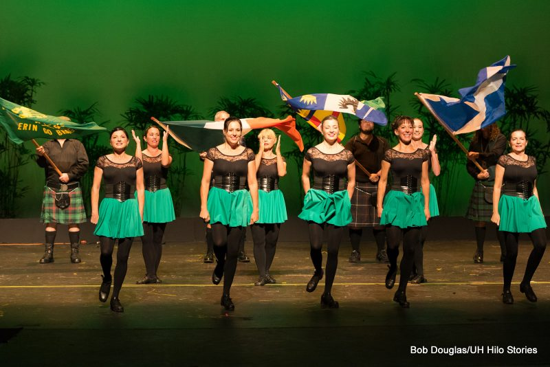 Women dancers in green skirts, black top and tights. Men in background with Irish flags.