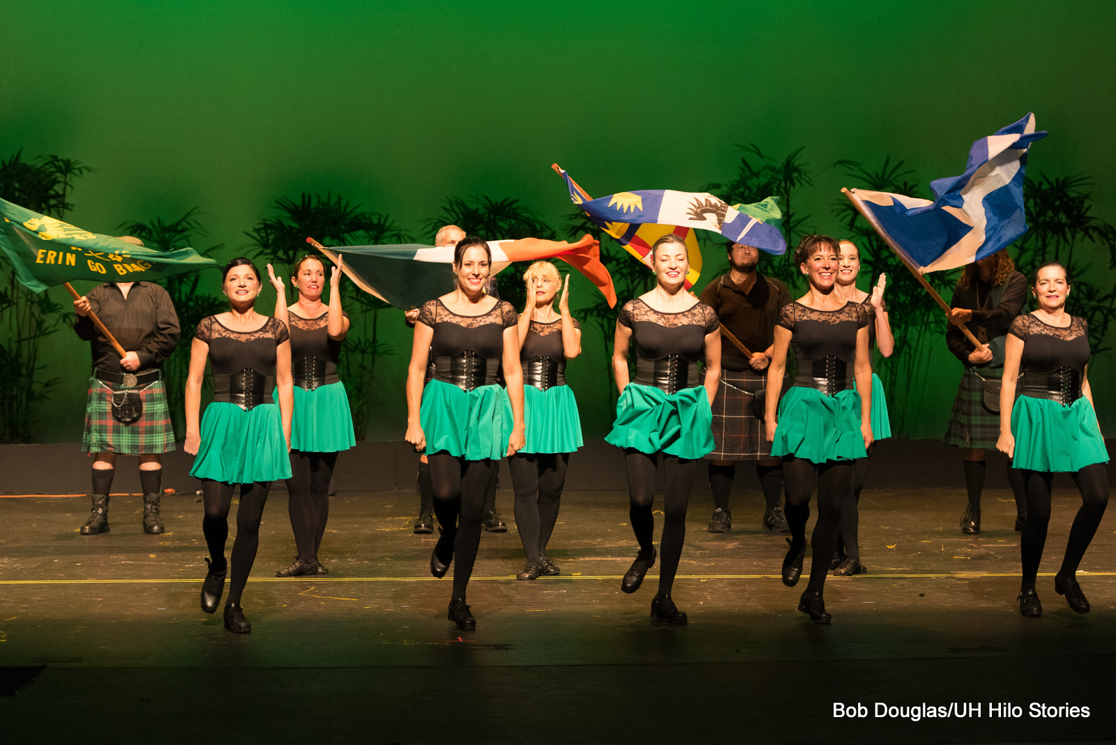 Line of female dancers in green skirts, black top and tights, shoes. They are doing Irish tap dance.