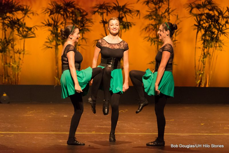 Women dancers in green skirts, black top and tights. Three women facing each other, each with one leg raised.