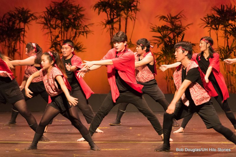 Men and women dancers, black and red, standing but feet far apart, arms extended.