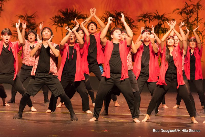 Male dancers arms above heads, They wear black and red.