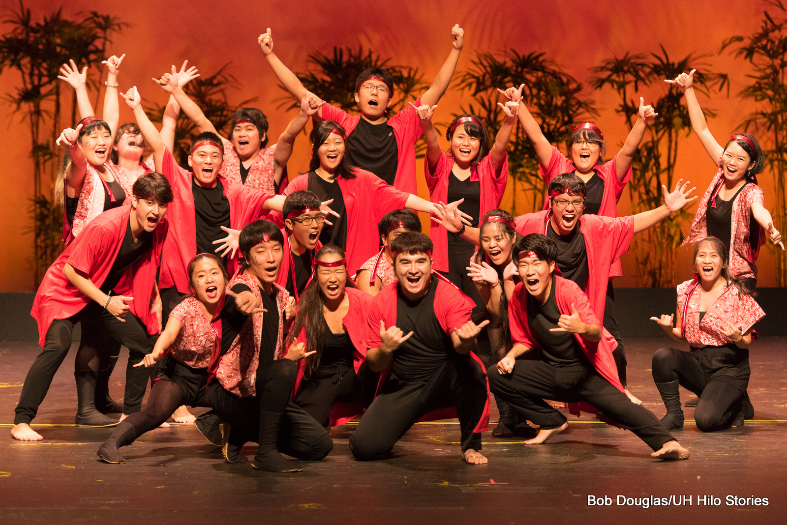 Group photo, lots of energy, hands thrown out in different directions. the dancers wear black and orange. Orange lighting.