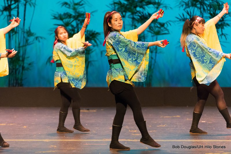 Women dancers black pants, yellow and green tops, holding red objects.