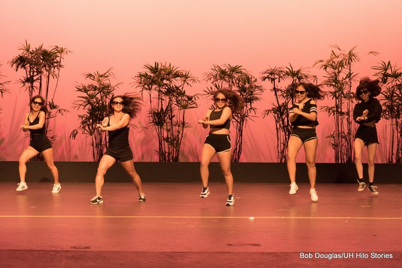 Female dancers in modern cheerleading costume doing modern dance.