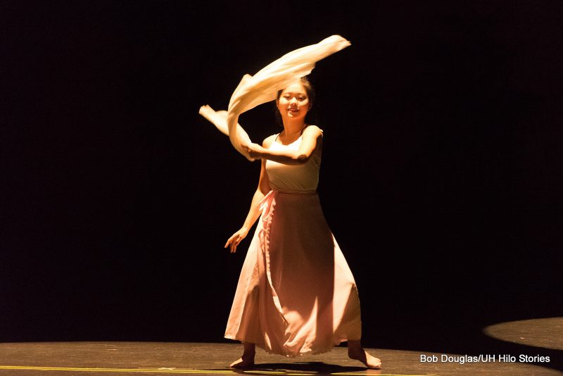 Solo female dancer in modern white gauze costume, graceful movements. Black background.