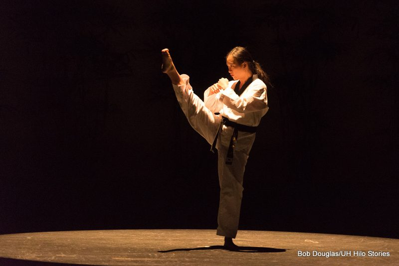 Female in martial arts attire, kicking straight up. Black background lighting.