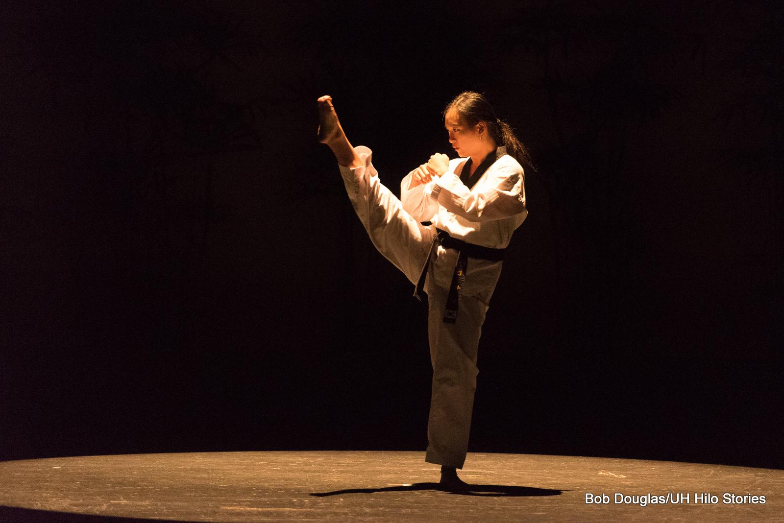 Woman in white kicks leg high in martial arts form.