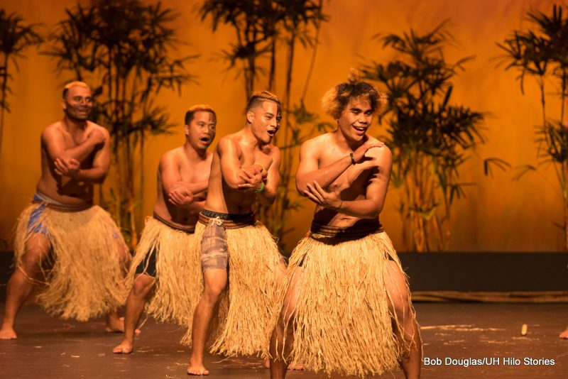 Line of males dancers in grass skirts, shirtless, tatoos on faces and arms.