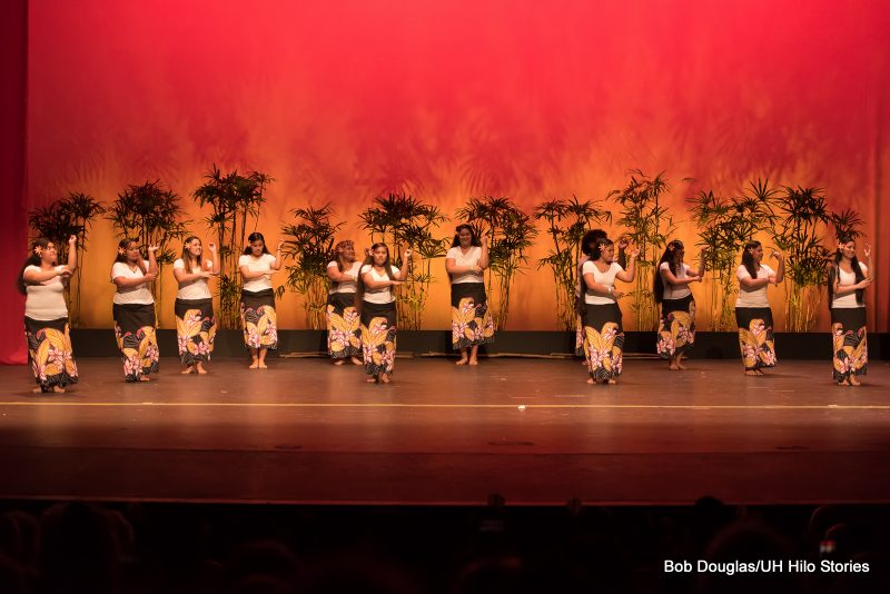 Women dancing in floral sarongs, white tops, stage is lit with orange.