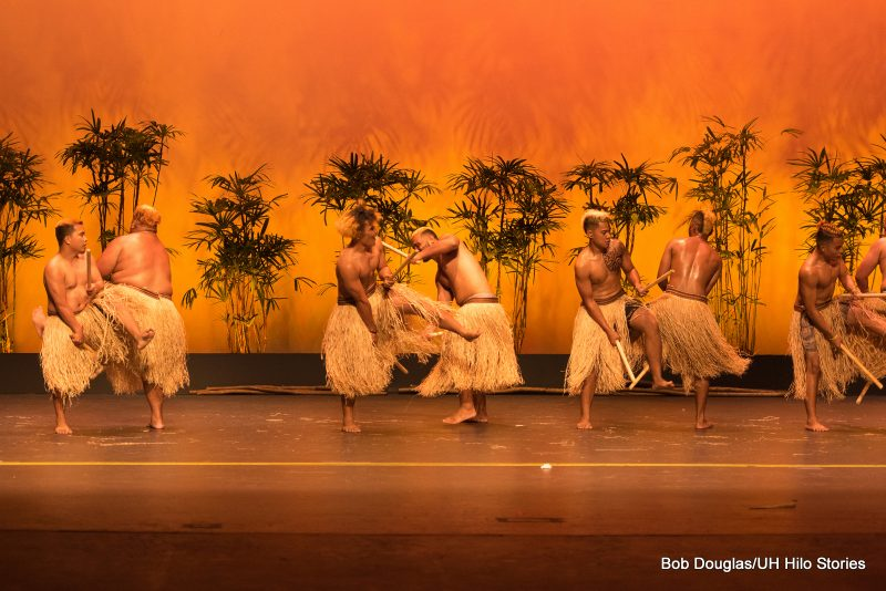 Males dancers in grass skirts, shirtless, tatoos on faces and arms, clicking sticks.