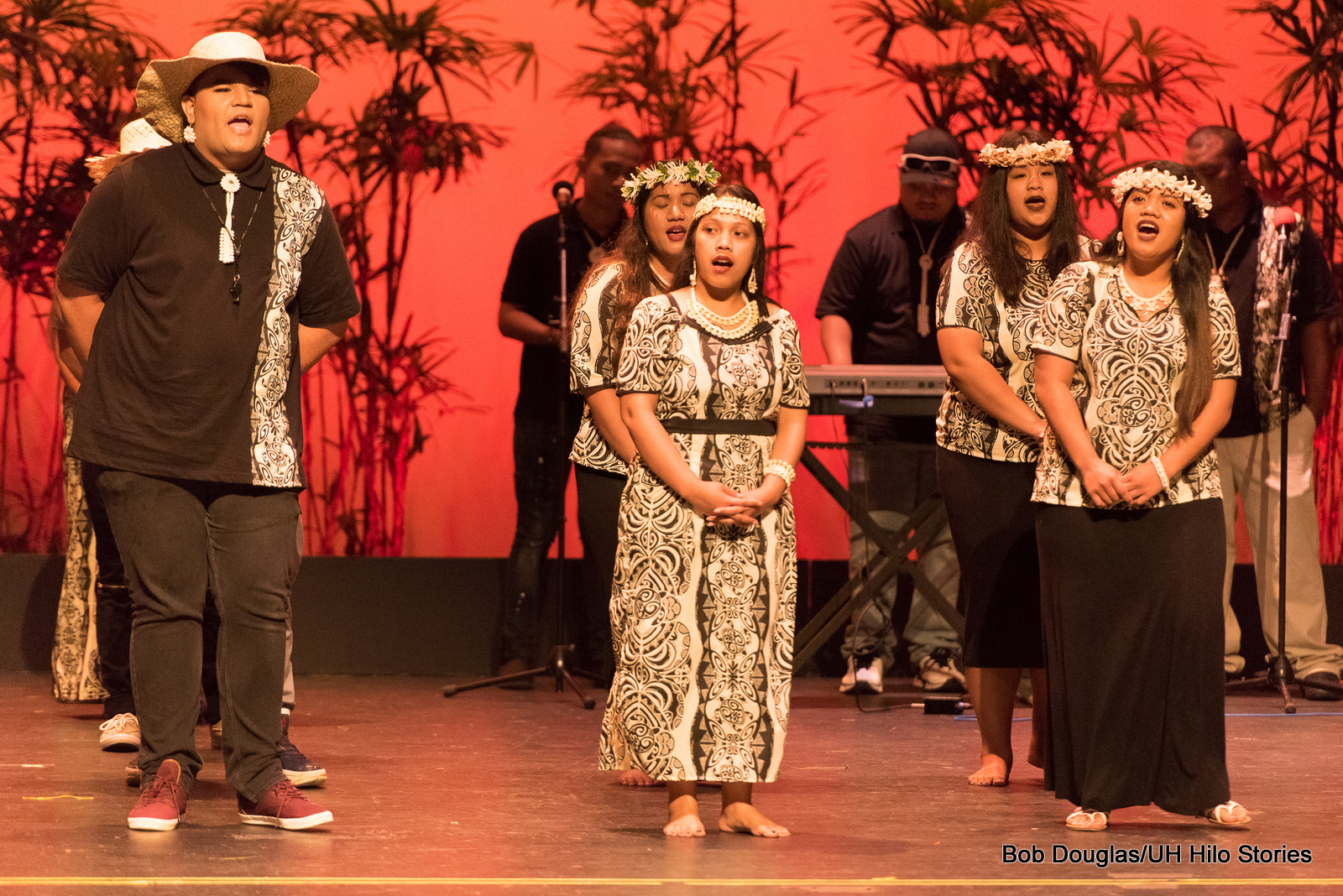 Group wearing black with ethnic print stripe on men's shirts and print on women's dresses. Men have hats, women shell hair band.