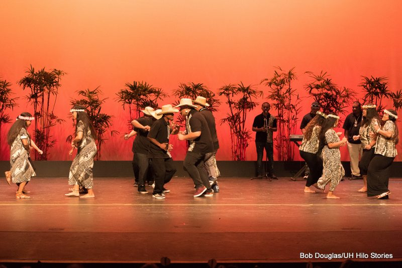 Group dancing wearing black with ethnic print stripe on men's shirts and print on women's dresses. Men have hats, women shell hair band.