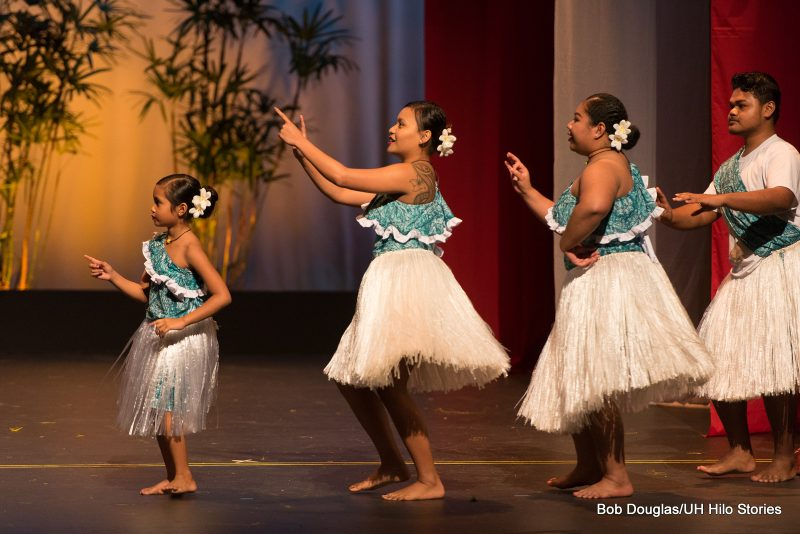 Women and little girl in teal blue tops with ethnic print, and white grass skirts, dancing, using arms and hand gestures.
