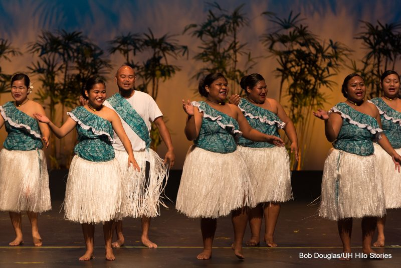 Group dancing, women in teal blue tops with ethnic print, and white grass skirts