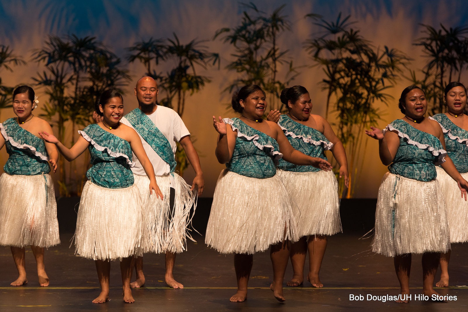 Group dancing, women in teal blue tops with ethnic print, and white grass skirts, Sweet and gentle dance.