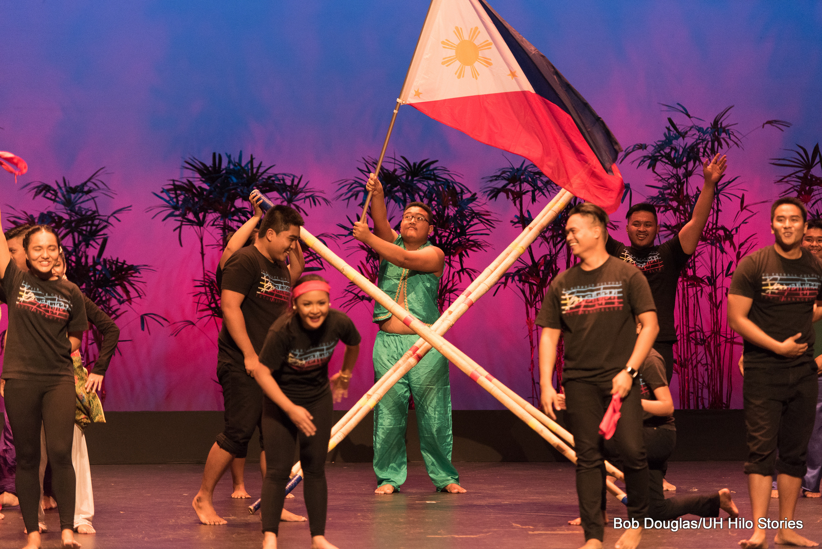 Group with male holding up Philippine flag. Two men holding crossed bamboo. Dancers are in black. Lighting is blue and pink.