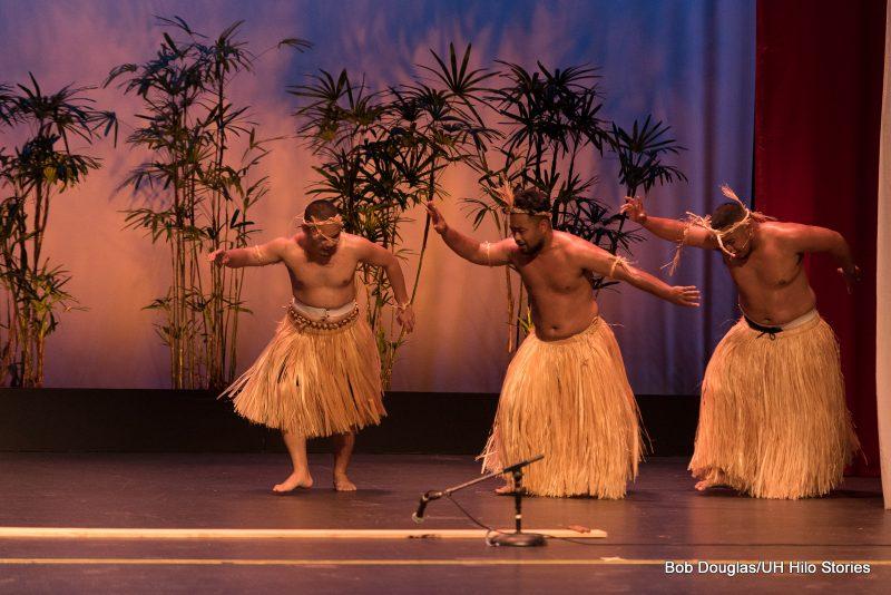 Men dancing, grass skirts.