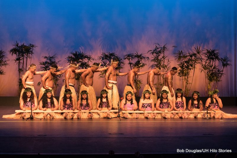Two lines of dancers: front is women seated, back is men standing turned stage left.