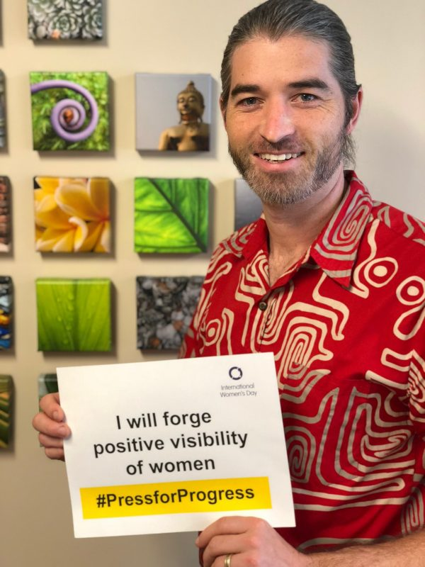 "Staff member Zach Street holding sign, ""I will forge positive visibility of women"""