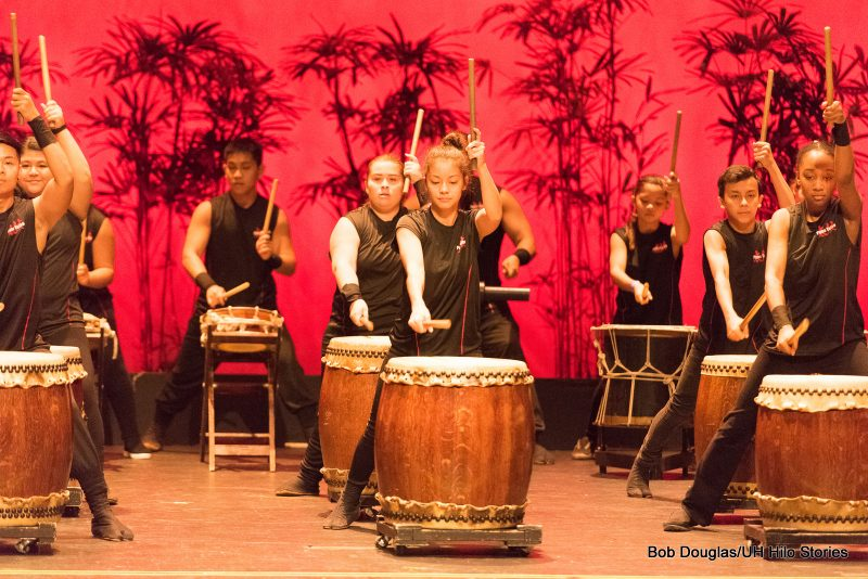 Group of men and women drumming traditional Japanese drums.. Red background.