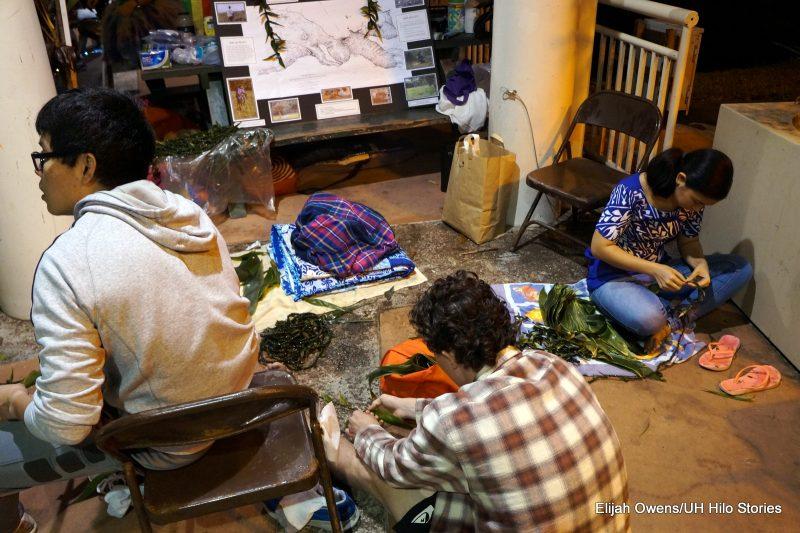 Students sitting on floor making ti lei.