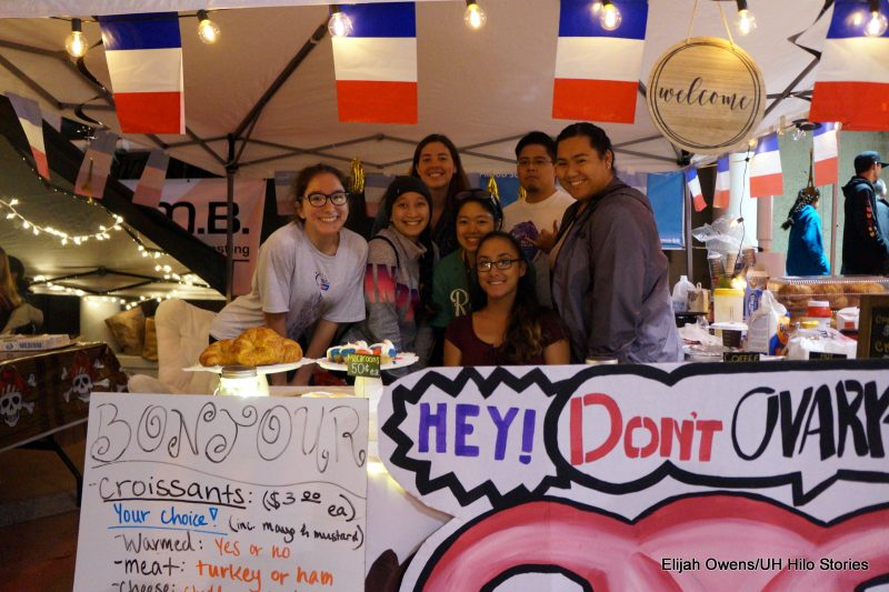 A group at a booth. Sign in front reads: HEY!