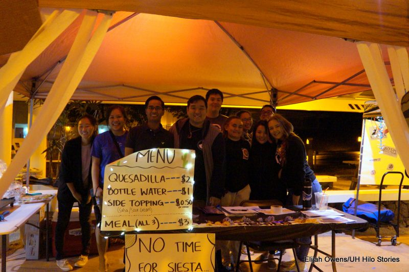 Group of students pose for photo at booth.