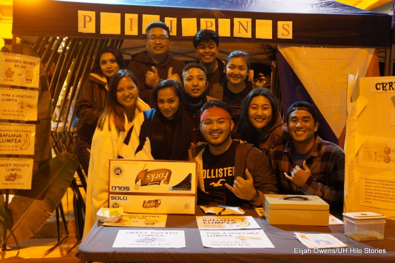 A large group of students pose for photo at their booth.