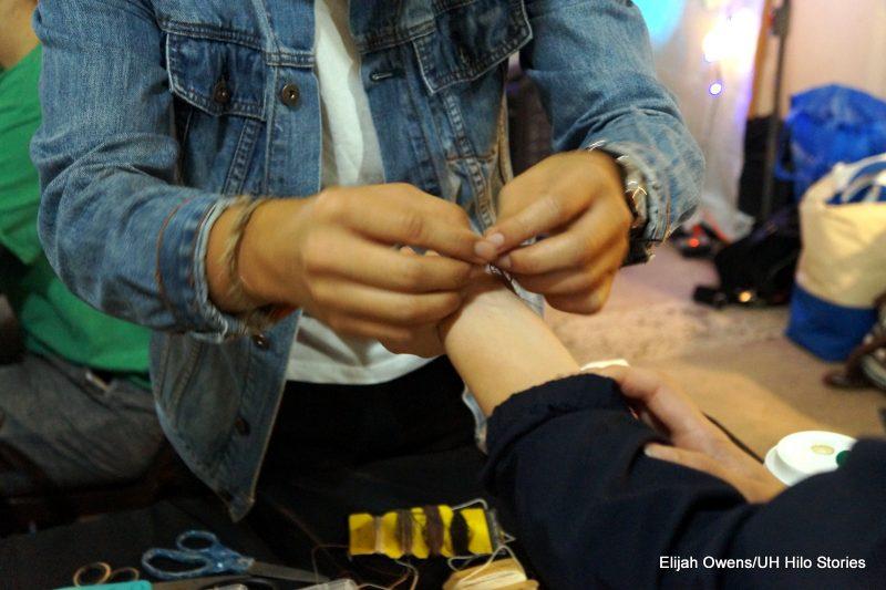 Hands fastening a bracelet.