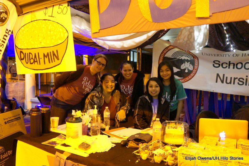 Group in booth with crafts on table.