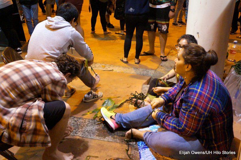 Students making ti leaf lei on floor of plaza.