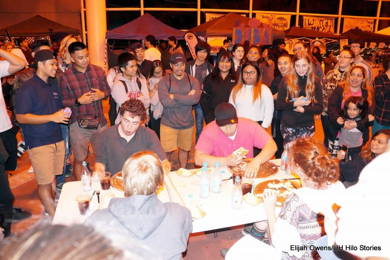 Eating contest, seated at table,everyone gathered around to watch.