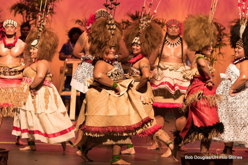 Large group dancing, fiber wraps, head dresses and adornments, male and female.