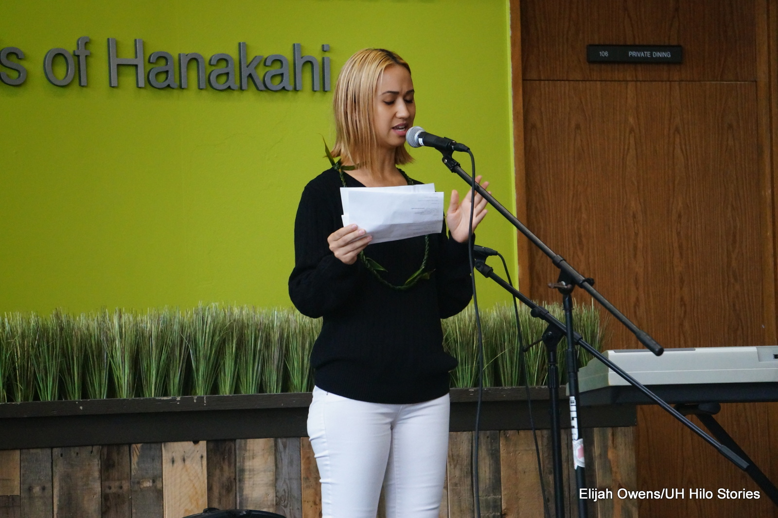 Young woman at mic, black top, white pants, reading from a piece of paper.