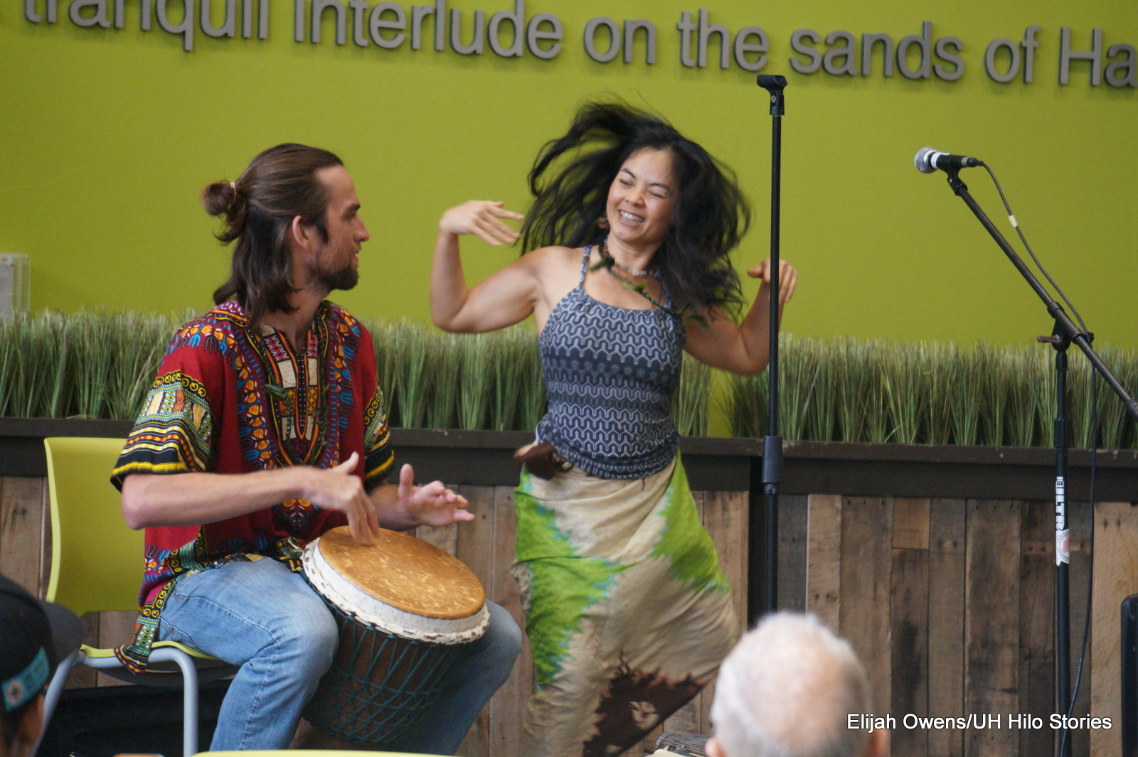Woman playing traditional Japanese string instrument. Man on drum. Woman doing enthusiastic dance in front of stage.