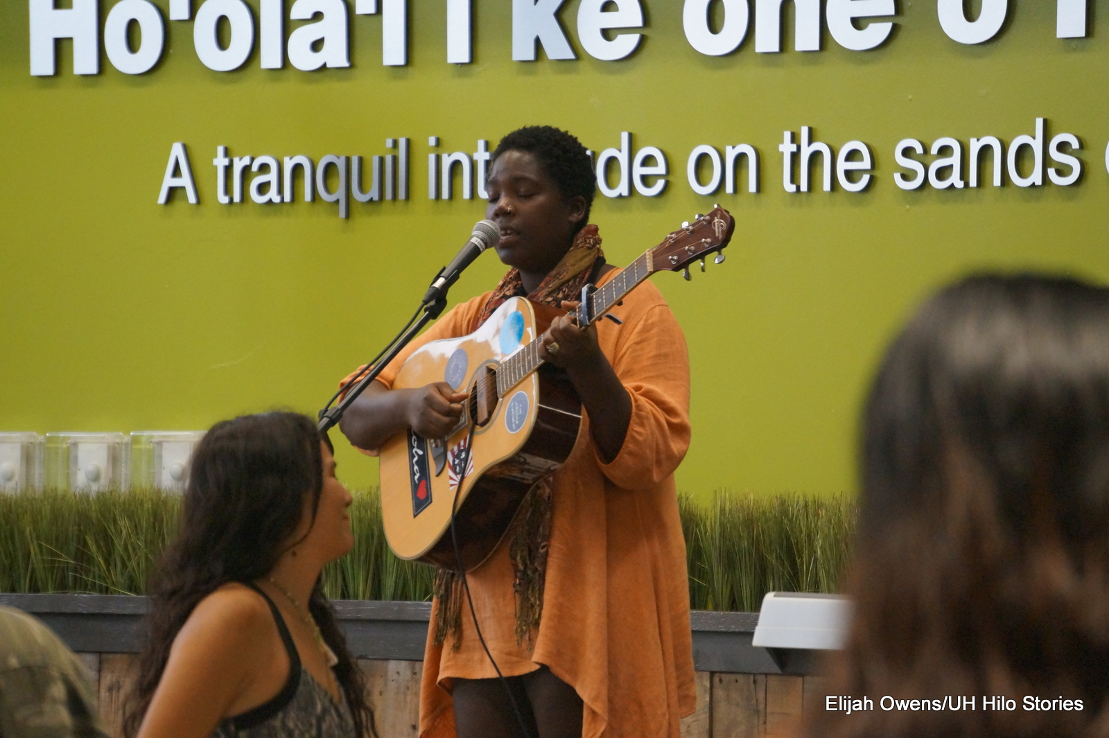 Solo woman playing guitar and singing.