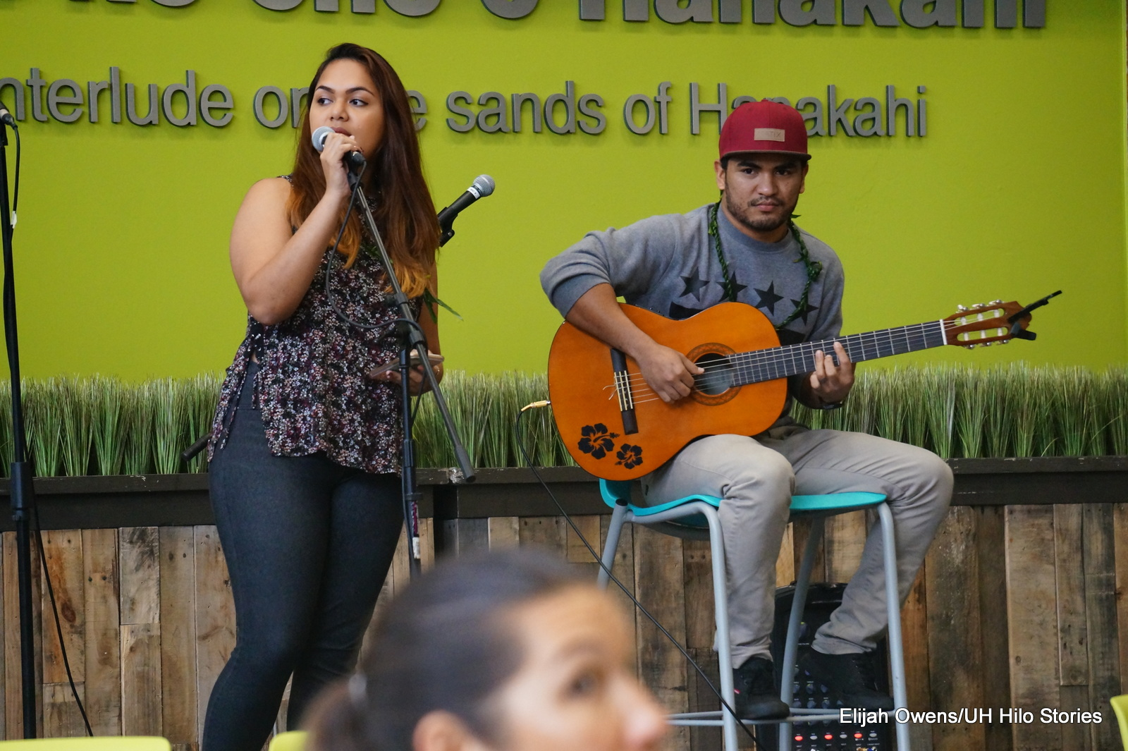 Woman standing at mic and man seated playing guitar.