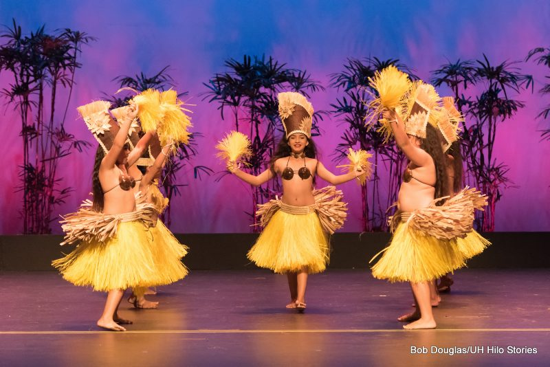 Lead female dancer emerges from center. Female dancers in grass skirts, in Tahitian tradition.