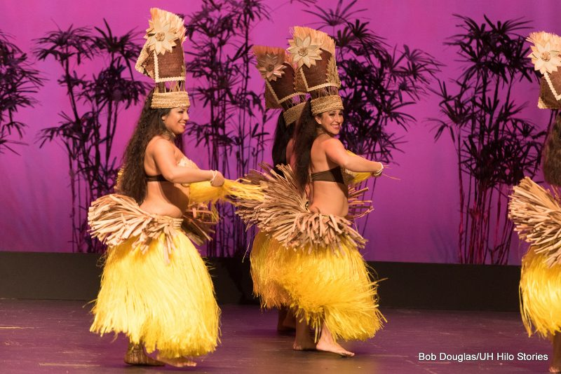 A side view of female dancers in grass skirts, in Tahitian tradition.