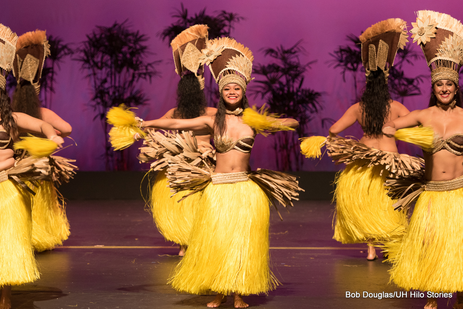 Female dancers in yellow grass skirts, tall head dresses, in Tahitian tradition.
