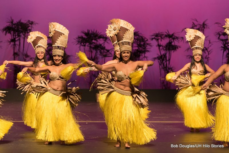 Close up of female dancers in yellow grass skirts, tall head dresses, in Tahitian tradition.