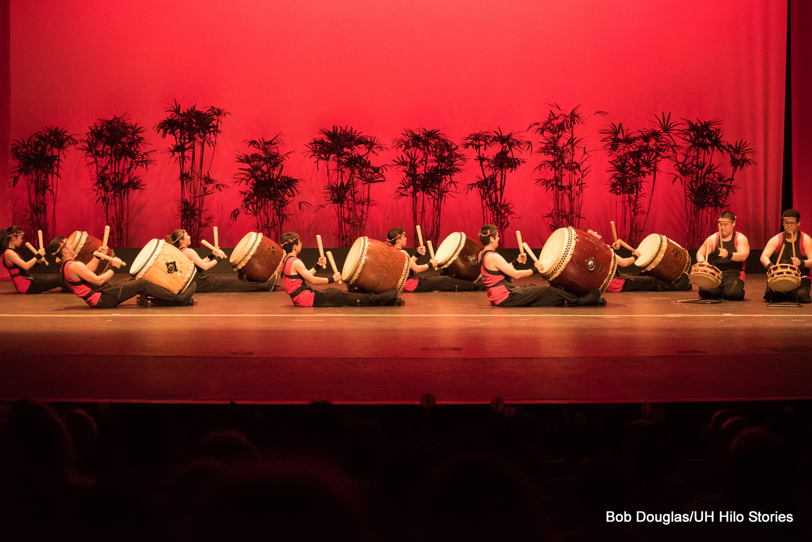 Group of Taiko drummers sit on floor, legs extended, beating drums. The light is red.