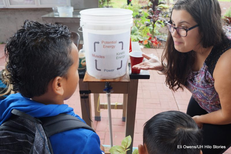 Instructor talks to boy about energy-- in background is a bucket with the words Potential Energy, Kinetic Energy, Power, Muscles.