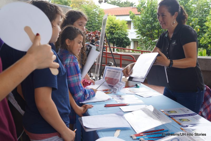 Schoolchildren looking at informational materials on a table.