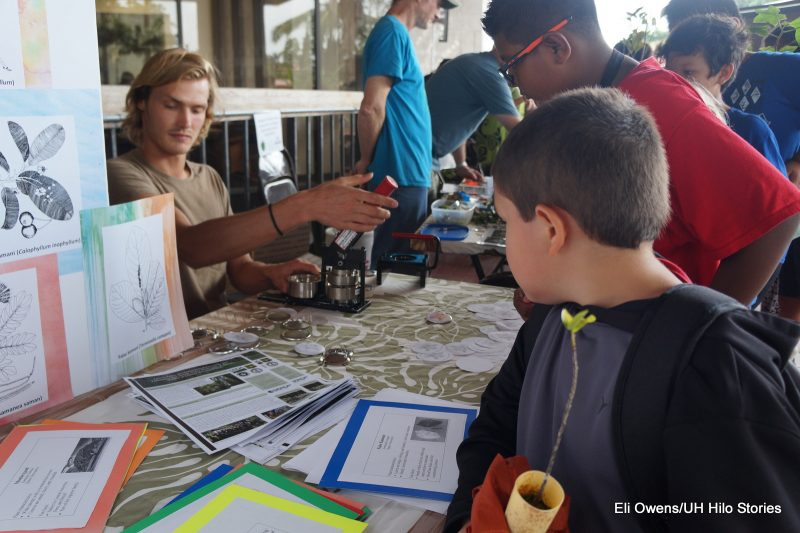 Young student looking at info materials on a table. In background is a microscope.