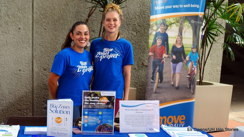 """Two women at BlueZones table. Book with title """"Blue Zones Solution."""" Poster with words: Move your way to well-being."""