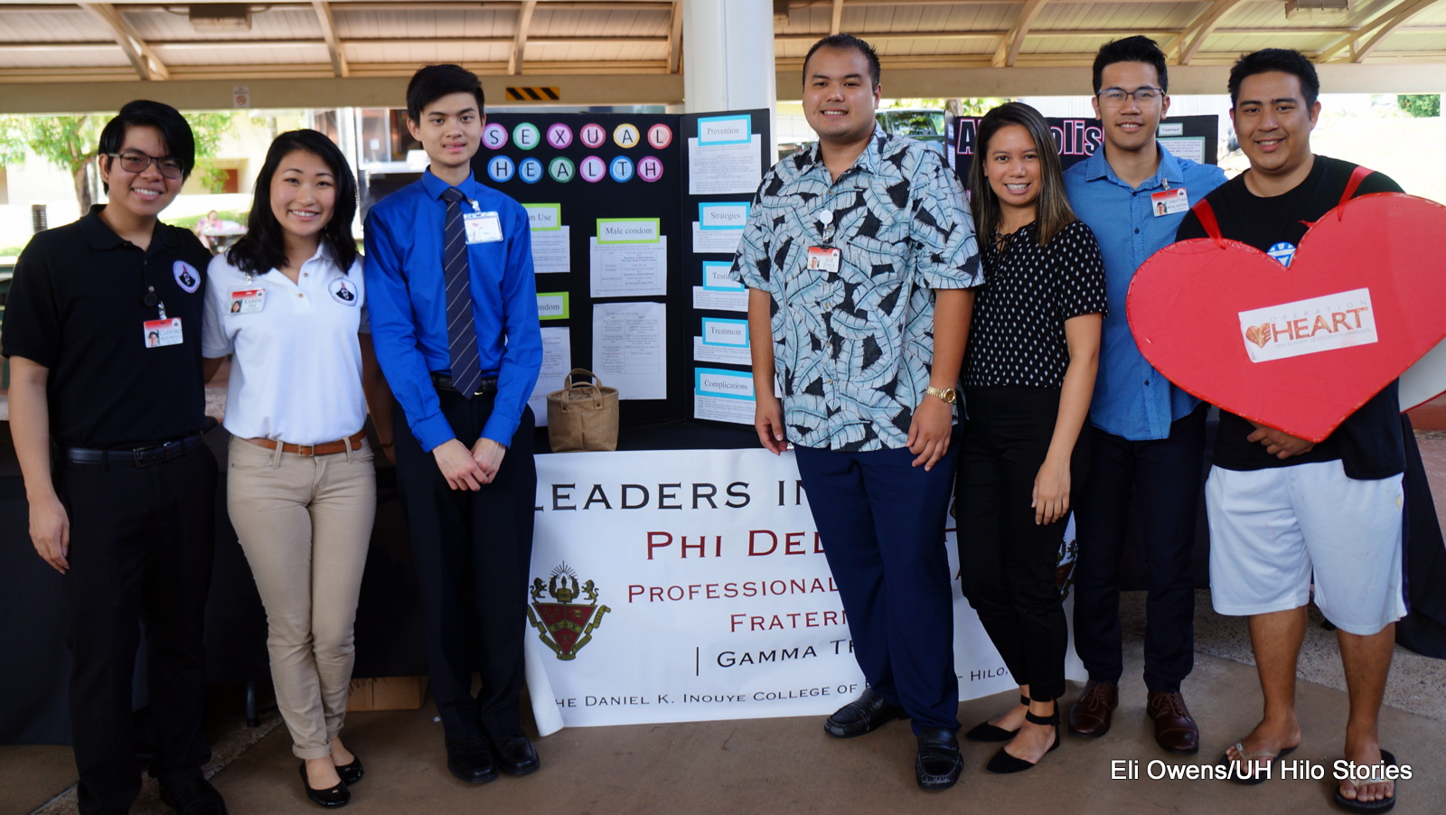 Group photo at informational table by fraternity leaders.