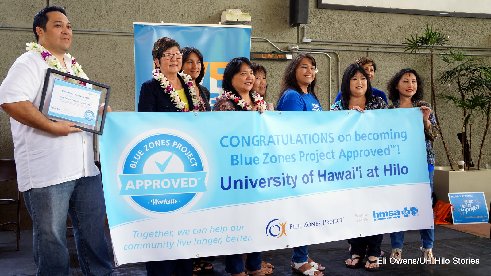 Group photo with banner: CONGRATULATIONS on becoming B;ue Zones Project Approved! University of Hawaii at Hilo. Together we can help our community live longer, better. Blue Zones Project logo and HMSA logo.